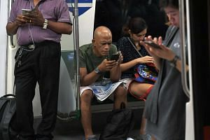 Commuters using their mobile phones in at MRT train.