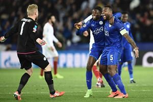 Leicester City's midfielder Wilfred Ndidi (centre), defender Wes Morgan (right) and goalkeeper Kasper Schmeichel (left) celebrating their victory at the final whistle during the Uefa Champions League match between Leicester City and Sevilla, on March