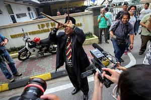 """Controversial Malaysian bomoh Ibrahim Mat Zin has sparked a media frenzy with yet another ritual. He turned up outside Kuala Lumpur Hospital on Monday and purported to be casting a spell with bamboo """"binoculars"""", to """"clear the path"""" for Mr Kim Jong N"""