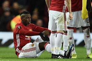 Manchester United's French midfielder Paul Pogba (L) sits on the pitch injured.