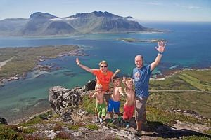 A family poses for a picture on a summit in Lofoten, Norway on July 19, 2014. Norway is the world's happiest country, according to the the World Happiness Report 2017.