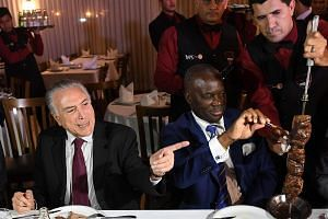 Brazil's President Michel Temer (left) and Angola's ambassador to Brazil Nelson Manuel Cosme eating barbecue in a steak house in Brasilia.