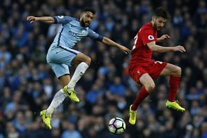 Liverpool's Adam Lallana dances in air with Manchester City's Gael Clichy in Sunday's (March 19) match.