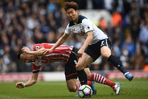 Southampton's Japanese defender Maya Yoshida (left) falls by Tottenham's South Korean striker Son Heung-Min during the match.