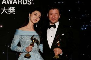 Japanese actor Tadanobu Asano and Chinese actress Fan Bingbing celebrate with their Best Actor and Best Actress awards at the Asian Film Awards in Hong Kong on March 21, 2017.