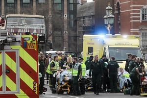 Members of the emergency services tend to individuals injured during an incident on Westminster Bridge near the Houses of Parliament in London.