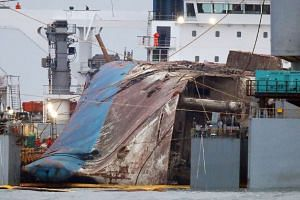 The wreck of the Sewol ferry, tied between two barges, is placed onto a submersible vessel before it is towed to the nearest port, off the coast of the southern South Korean island of Jindo on Saturday (March 25).