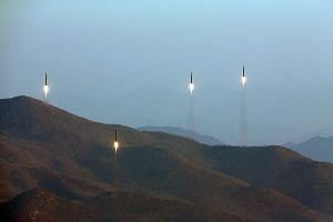 An undated photo made available by the North Korean Central News Agency on March 7 shows four projectiles during a ballistic rocket launching drill of Hwasong artillery units of the Strategic Force of the Korean People's Army at an undisclosed locati