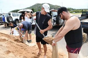 People fill up sandbags in preparation for Cyclone Debbie in Townsville, Queensland.