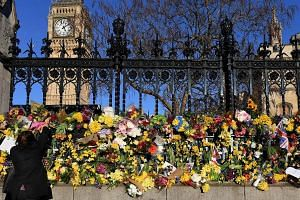 A wellwisher lays flowers outside the Houses of Parliament, following the March 22 terror attack.