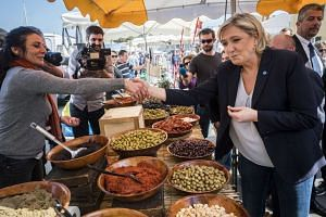 Le Pen (centre) visiting a local market in Le Brusc, southern France, during her presidential campaign.