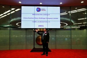 A file photo of Mr Yang Kai, chairman and CEO of China Huishan Dairy, taking part in a ceremony during the debut of the company at the Hong Kong Exchanges Sept 27, 2013.