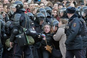 Russian riot policemen detain a demonstrator during an opposition rally in central Moscow.