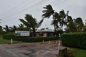 Palm trees blowing in the wind in the town of Ayr in far north Queensland as Cyclone Debbie approaches, on March 28, 2017.