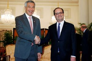 French President Francois Hollande with Singapore's Prime Minister Lee Hsien Loong at the Istana in Singapore on March 27, 2017.