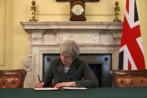 British Prime Minister Theresa May signs the official letter to European Council President Donald Tusk invoking Article 50 and the United Kingdom's intention to leave the EU on March 28, 2017.