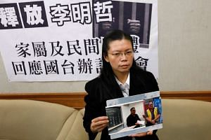 Li Ching-yu holdings photos of her husband, Taiwanese human rights activist Li Ming-che, during a news conference in Taipei, Taiwan, on March 29, 2017.