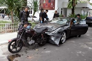 Thai police officers examine a damaged Ferrari at the home of the late Red Bull founder Chaleo Yoovidhaya in Bangkok on Sept 3, 2012.