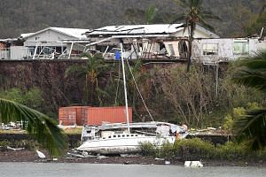 A boat seen smashed against the bank at Shute Harbour near Airlie Beach in north Queensland yesterday. Cyclone Debbie struck the Queensland coast at about midday on Tuesday, uprooting trees, washing boats ashore and ripping roofs off buildings. Farme