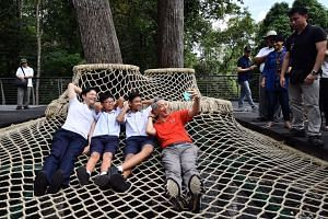 (From left) Mr Lawrence Wong, Minister for National Development and Second Minister for Finance, Casey Lim and Muhammad Nabil Bin Ali, both from Tanglin Secondary School, and Prime Minister Lee Hsien Loong on the Canopy Web at the SPH Walk of Giants