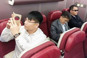 Passengers believed to be North Koreans, including murder suspect Kim Uk Il (far left), in a plane bound for Beijing, at an airport in Kuala Lumpur on Thursday.