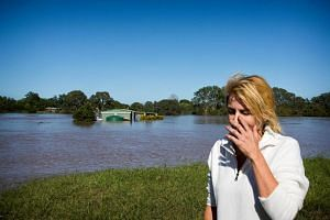 Kaycee Bentley reacts to the discovery of her flooded home in North MacLean, Brisbane on April 1, 2017, which was submerged under floodwaters caused by Cyclone Debbie.