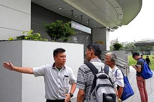 An SBS Transit staff member directing people to alternative transport routes at Hougang MRT station on Sunday. The station was shut and passengers were evacuated when a 39-year-old Chinese national caused a security scare after leaving an unattended