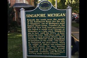 A sign showing a plaque for the historical ghost town of Singapore, Michigan.