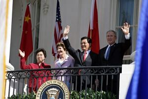 Mr Bush and Mr Hu with their wives, Laura Bush and Liu Yongqing, wave from the White House's South Portico balcony after the arrival ceremony for Mr Hu on April 20, 2006.