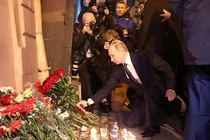 Russian President Vladimir Putin placing flowers in memory of victims of the blast in the St Petersburg metro outside Technological Institute station, on April 3, 2017.