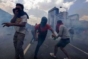 People take cover from teargas during a protest against the Venezuelan Government in Caracas, Venezuela, on April 6, 2017.