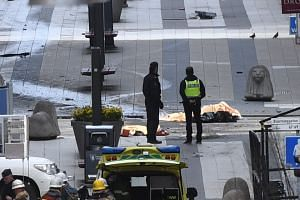 The bodies of victims covered by blankets on the ground in central Stockholm after a truck crashed into a department store in central Stockholm, Sweden, on April 7, 2017.