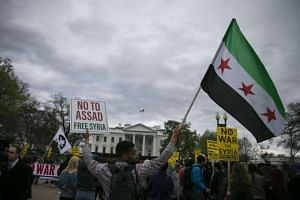 A demonstrator holding the Free Syrian Army flag in a protest against the overnight US military action in Syria, outside the White House in Washington, on April 7, 2017.