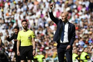 Real's Zidane (right) gestures from the sideline during the Spanish league football match against Atletico Madrid.