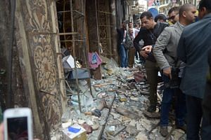 People look at the damage caused by the bomb in front of a church in Alexandria.
