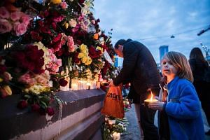 Well wishers place flowers and candles at a makeshift memorial outside the Stockholm department store on April 8, 2017.