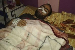 Mr Ebrahim Abbas recovering in a hospital in Syria from a gunshot wound inflicted by a sniper, in an undated photo. He is now in Turkey, and says the US strike on the Syrian regime gives him hope.