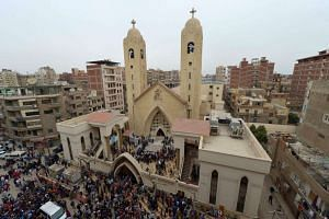 A general view shows people gathering outside the Mar Girgis Coptic Church in the Nile Delta City of Tanta, 120km north of Cairo, after a bomb blast struck worshippers gathering to celebrate Palm Sunday, on April 9, 2017.