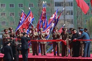 North Korean leader Kim Jong Un (second from right) cuts the ribbon for an opening ceremony of a new residential housing project on Ryo Myong street in Pyongyang, on April 13, 2017.