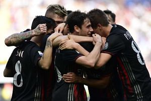 AC Milan celebrate after Carlos Bacca scored during their Italian Serie A football match against Palermo on April 9, 2017.