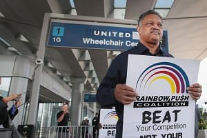 Civil rights leader Jesse Jackson leading a protest at O'Hare International Airport on Wednesday. Some US lawmakers have called for new rules on airlines' overbooking of flights.