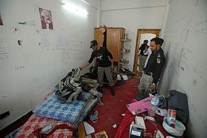 Police yesterday searching the hostel room of Mr Mashal Khan, who was killed by a mob of fellow students at Abdul Wali Khan University in Mardan, Pakistan. At least 11 students have been arrested so far.