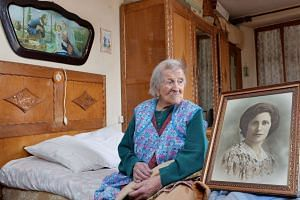 A 2016 file photo shows Emma Morano, then aged 116, in her apartment in Italy with a picture depicting her where she was young.