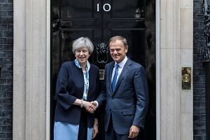 British Prime Minister Theresa May shakes hands with Donald Tusk, president of the European Union, outside number 10 Downing Street in London on April 6, 2017.
