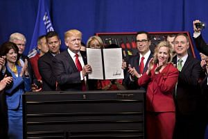 """US President Donald Trump displaying a signed executive order which pushes for the government to """"Buy American"""" products, such as iron, steel and manufactured goods."""
