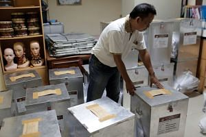 An election official preparing ballot boxes before distributing them to polling stations, in Jakarta, Indonesia, on April 18, 2017.
