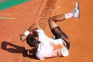Djokovic falls during the match against Belgium's David Goffin.