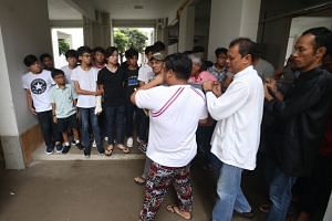 Relatives and friends grieve as the body of Muhammad Hambali Sumathi arrives at his aunt's Eunos Road home at about 2pm.