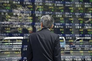 A man looks at an electric quotation board flashing the Nikkei key index of the Tokyo Stock Exchange in Tokyo, on April 12, 2017.