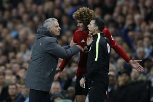 Manchester United's Marouane Fellaini (centre) after being sent off with manager Jose Mourinho (left) and fourth official Neil Swarbrick.